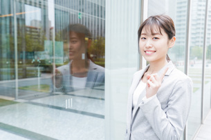 オフィス街を歩く若いビジネスウーマンの写真素材 [FYI04713630]