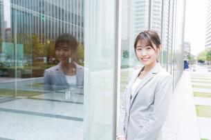 オフィス街を歩く若いビジネスウーマンの写真素材 [FYI04713632]