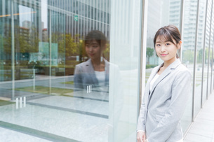 オフィス街を歩く若いビジネスウーマンの写真素材 [FYI04713637]