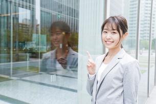 オフィス街を歩く若いビジネスウーマンの写真素材 [FYI04713638]