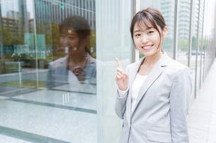 オフィス街を歩く若いビジネスウーマンの写真素材 [FYI04713642]