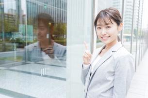 オフィス街を歩く若いビジネスウーマンの写真素材 [FYI04713643]