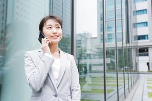 オフィス街で電話をする若いビジネスウーマンの写真素材 [FYI04713656]