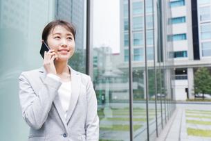 オフィス街で電話をする若いビジネスウーマンの写真素材 [FYI04713657]
