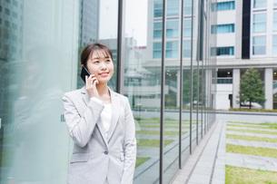 オフィス街で電話をする若いビジネスウーマンの写真素材 [FYI04713662]