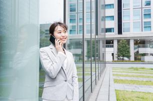 オフィス街で電話をする若いビジネスウーマンの写真素材 [FYI04713670]