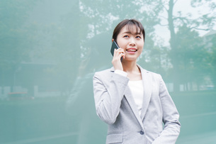 オフィス街で電話をする若いビジネスウーマンの写真素材 [FYI04713677]