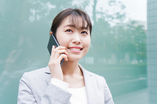 オフィス街で電話をする若いビジネスウーマンの写真素材 [FYI04713680]
