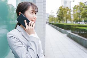 オフィス街で電話をする若いビジネスウーマンの写真素材 [FYI04713685]