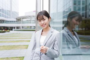 オフィス街でキャッシュレス決済をするビジネスウーマンの写真素材 [FYI04713703]