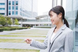 オフィス街でキャッシュレス決済をするビジネスウーマンの写真素材 [FYI04713708]