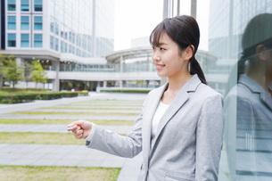 オフィス街でキャッシュレス決済をするビジネスウーマンの写真素材 [FYI04713709]