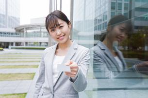 オフィス街でキャッシュレス決済をするビジネスウーマンの写真素材 [FYI04713711]