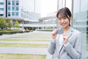 オフィス街でキャッシュレス決済をするビジネスウーマンの写真素材 [FYI04713719]