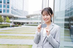 オフィス街でキャッシュレス決済をするビジネスウーマンの写真素材 [FYI04713724]