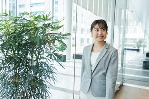 オフィス内を歩く若いビジネスウーマンの写真素材 [FYI04713726]