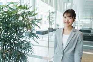 オフィス内を歩く若いビジネスウーマンの写真素材 [FYI04713727]