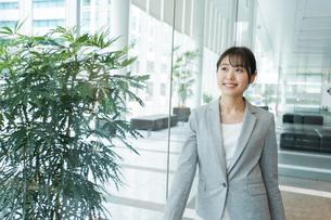 オフィス内を歩く若いビジネスウーマンの写真素材 [FYI04713728]