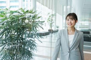 オフィス内を歩く若いビジネスウーマンの写真素材 [FYI04713730]