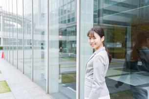 オフィス街を歩く若いビジネスウーマンの写真素材 [FYI04713733]