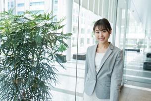 オフィス内を歩く若いビジネスウーマンの写真素材 [FYI04713734]