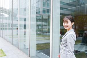 オフィス街を歩く若いビジネスウーマンの写真素材 [FYI04713737]