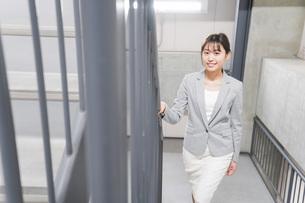 オフィス内を歩く若いビジネスウーマンの写真素材 [FYI04713738]