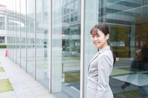 オフィス街を歩く若いビジネスウーマンの写真素材 [FYI04713744]