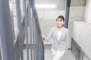 オフィス内を歩く若いビジネスウーマンの写真素材 [FYI04713746]