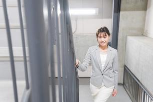 オフィス内を歩く若いビジネスウーマンの写真素材 [FYI04713750]