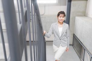 オフィス内を歩く若いビジネスウーマンの写真素材 [FYI04713751]