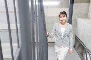 オフィス内を歩く若いビジネスウーマンの写真素材 [FYI04713756]