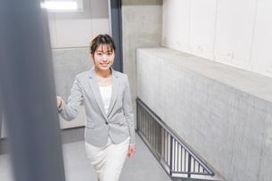 オフィス内を歩く若いビジネスウーマンの写真素材 [FYI04713759]