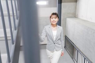 オフィス内を歩く若いビジネスウーマンの写真素材 [FYI04713760]