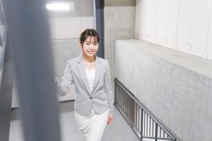 オフィス内を歩く若いビジネスウーマンの写真素材 [FYI04713768]