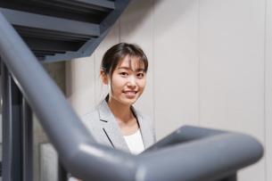 オフィス内を歩く若いビジネスウーマンの写真素材 [FYI04713769]