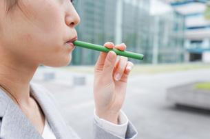 電子タバコを吸う若いビジネスウーマンの写真素材 [FYI04713787]