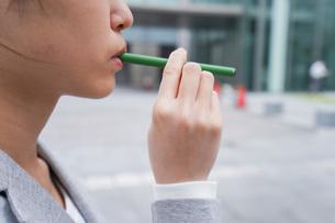 電子タバコを吸う若いビジネスウーマンの写真素材 [FYI04713788]