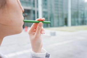 電子タバコを吸う若いビジネスウーマンの写真素材 [FYI04713793]