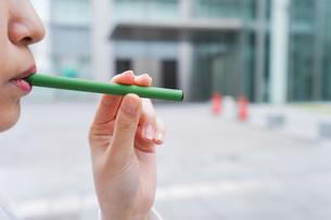 電子タバコを吸う若いビジネスウーマンの写真素材 [FYI04713796]