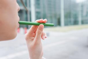 電子タバコを吸う若いビジネスウーマンの写真素材 [FYI04713797]