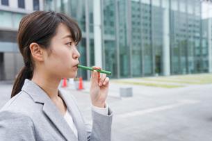 電子タバコを吸う若いビジネスウーマンの写真素材 [FYI04713803]
