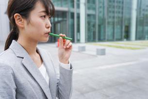 電子タバコを吸う若いビジネスウーマンの写真素材 [FYI04713805]