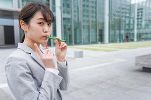電子タバコを吸う若いビジネスウーマンの写真素材 [FYI04713806]