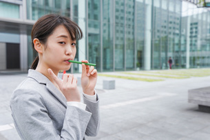 電子タバコを吸う若いビジネスウーマンの写真素材 [FYI04713815]