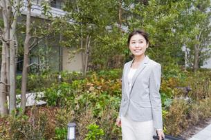オフィス街を歩く若いビジネスウーマンの写真素材 [FYI04713822]