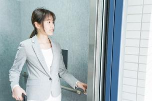 エレベーターを使う若いビジネスウーマンの写真素材 [FYI04713838]