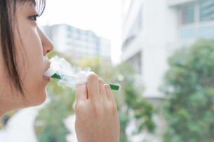 電子タバコを吸う若いビジネスウーマンの写真素材 [FYI04713841]