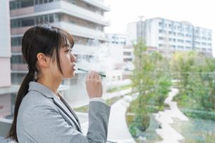 電子タバコを吸う若いビジネスウーマンの写真素材 [FYI04713842]