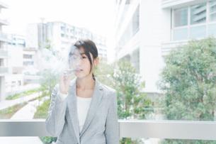 電子タバコを吸う若いビジネスウーマンの写真素材 [FYI04713845]